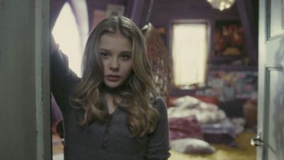 Chloe Grace Moretz leaning in the doorway of her bedroom.