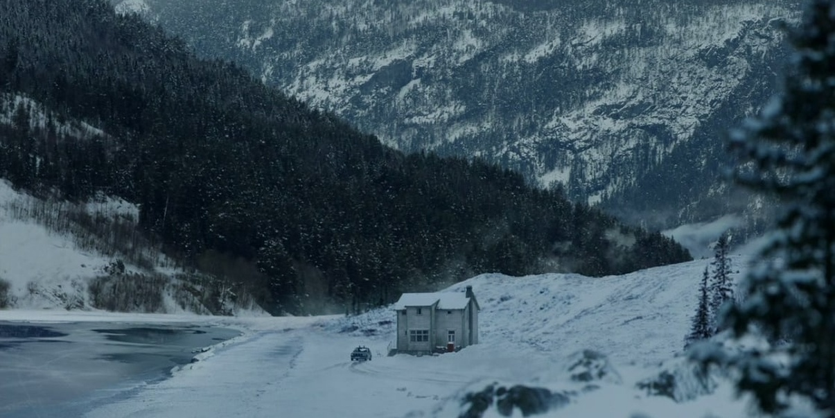 A single house with a car out front with a lake to the left and mountains in the background, snow on the ground and some in the mountains