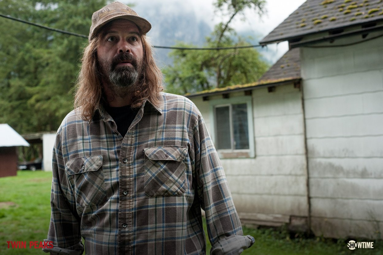 The Farmer stands in front of his house wearing a checkered buttondown shirt, baseball style hat, long shoulder length hair and a beard.