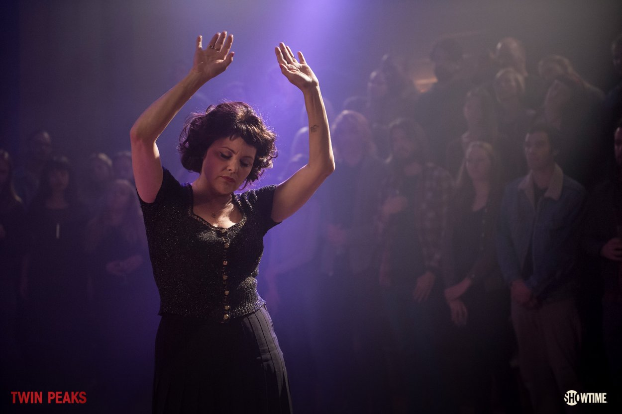 Audrey dances over a purple light, her arms upraised and she's lost in feeling.