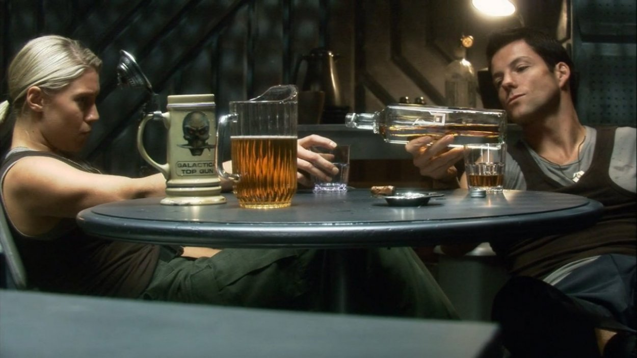 Lee pours Starbuck a drink in the mess on Galactica