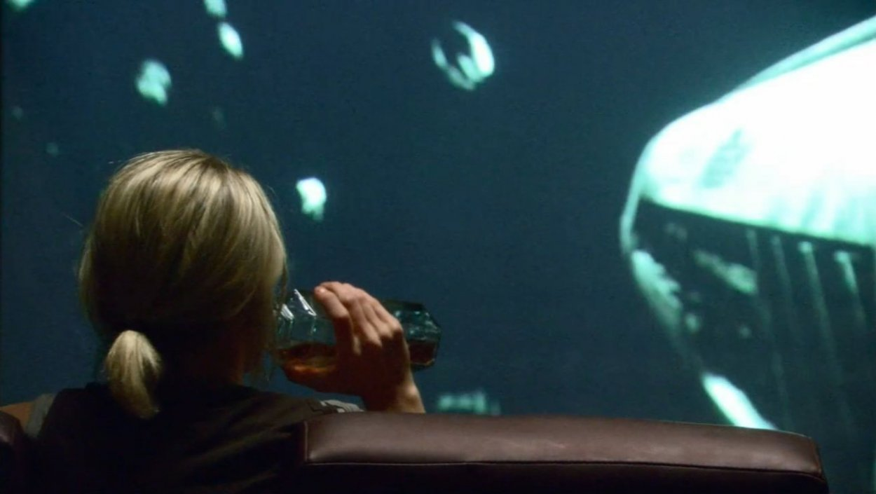 Starbuck drinks alone in the briefing room watching footage of Scar