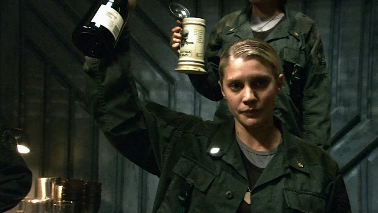Kat stands behind Starbuck who raises a bottle to salute the fallen pilots
