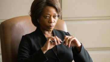 Alfre Woodard listens to the pleas of a inmate's family at her desk.