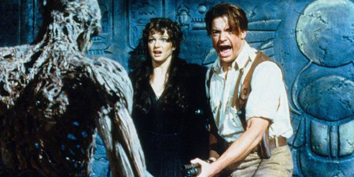Evelyn backed against the wall in horror, Rick holding a gun with his mouth open in a scream, both staring straight ahead at the mummy, whose back is to the picture