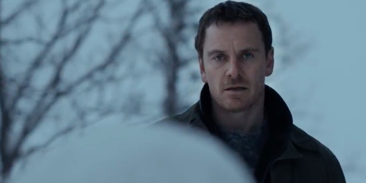 Michael Fassbender In The Snowman looking at the snowman in the forefront of the picture, its back to the viewer with trees behind Fassbender and a white cloudy background