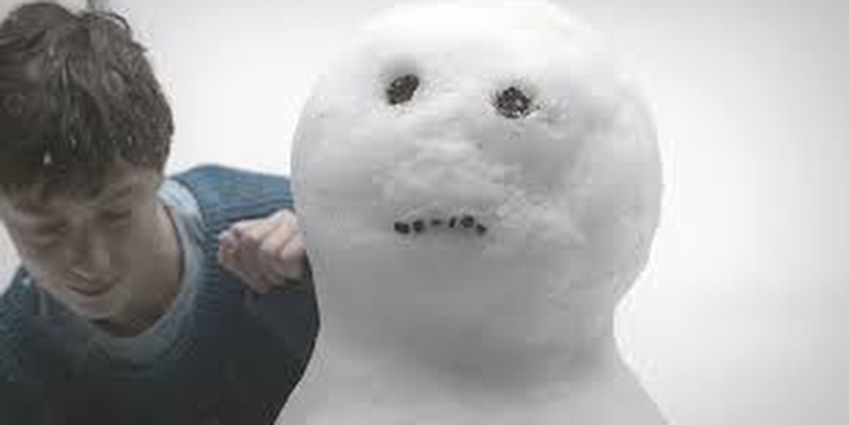 A young boy with brunette hair looking down, his hand in a fist and resting upon the shoulder of a snowman with only its head showing with two black eyes and a straight mouth with snow in the background