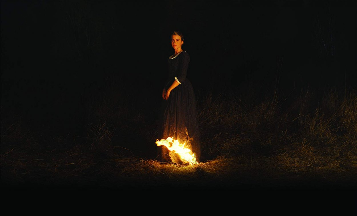a woman stands in the dark with the tail of her dress on fire