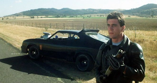 """Mad"" Max Rockatansky holds his gun while standing next to his black vehicle"