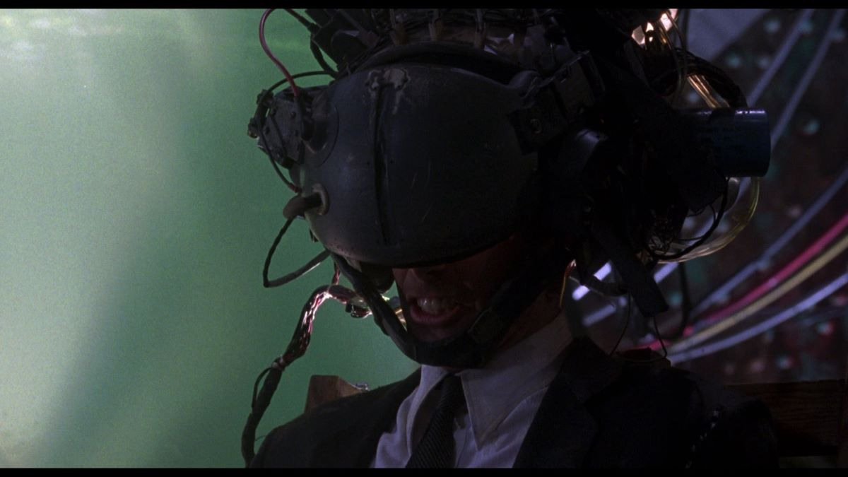Johnny wears a virtual-reality helmet to try to download his brain data in the climax of Johnny Mnemonic