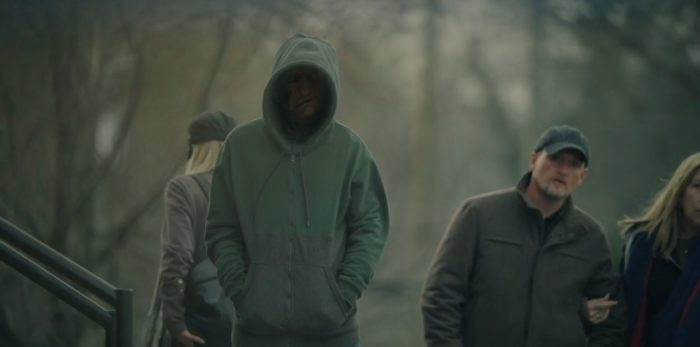 Mysterious figure in a green hoodie looks on to the scene of a shooting