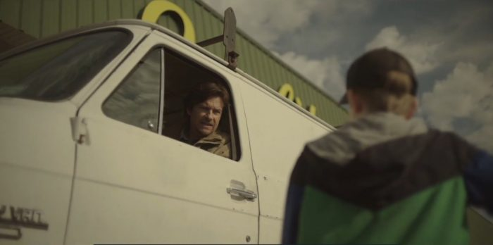 Terry driving a white van looks out the window and Frankie Peterson