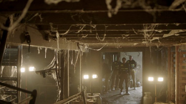 Police enter a decrepit barn to begin their search