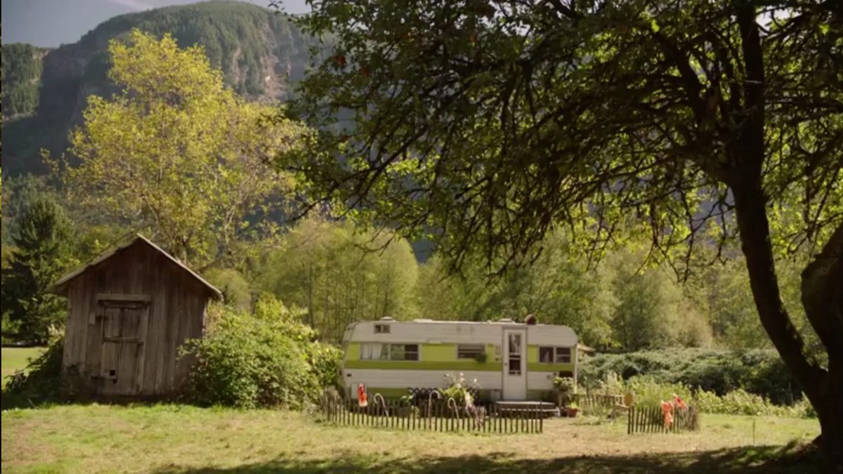 Twin Peaks Part 10 - A small older looking trailer sits in an idylic pasture, an old farm shed sitting beside it, mountains in the background