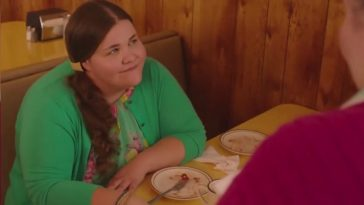 Twin Peaks Part 6 - Miriam sits smiling at a booth in the RR Diner, two polished off pie plates sitting in front of her