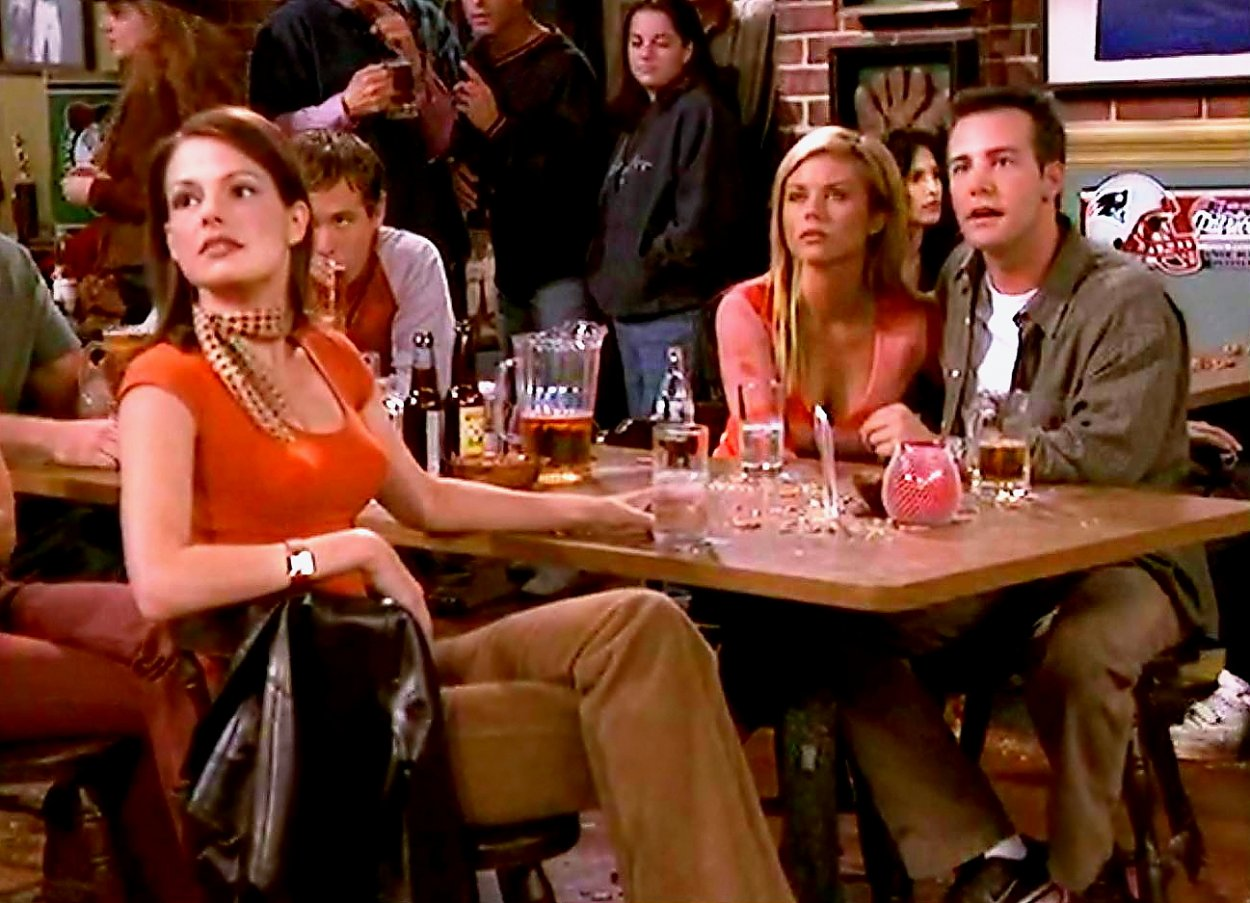Ashley, Marti and Pete stare at something while sitting in a bar