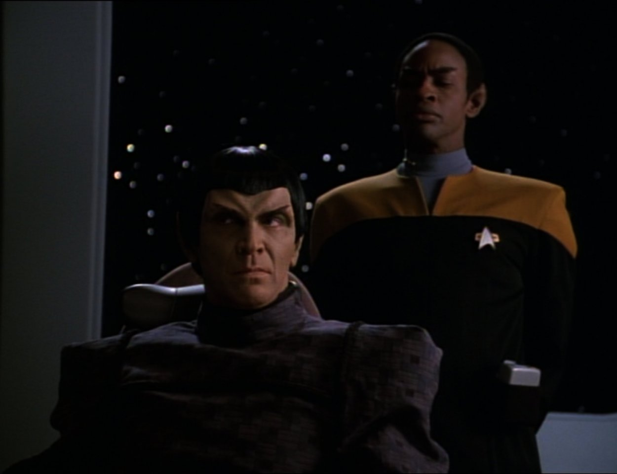 Tuvok stands behind a Romulan