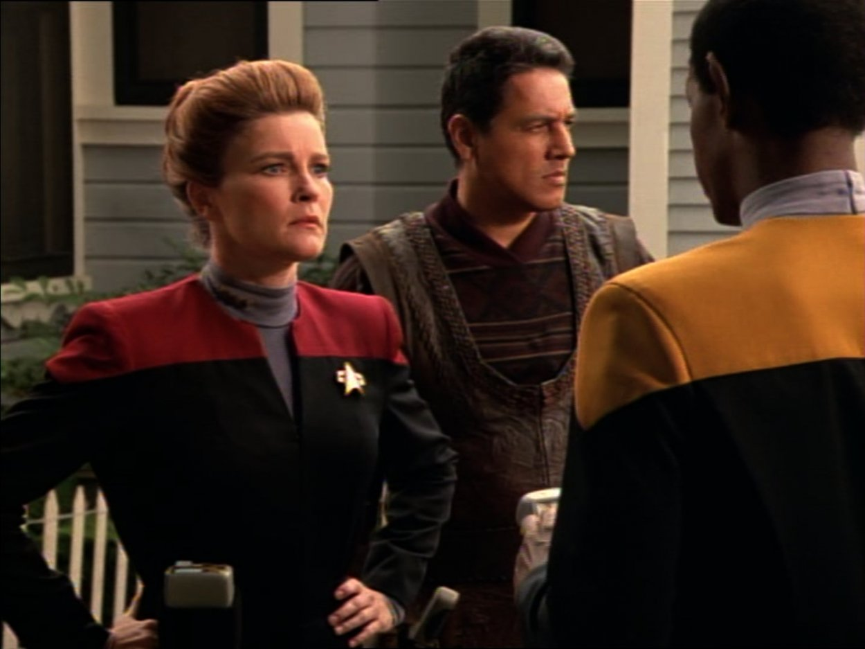 Janeway, Chakotay and Tuvok stand outside a house with a white picket fence