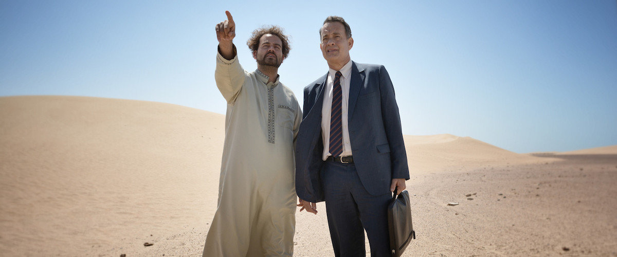 alan clay standing in the desert with his driver, yousef who is pointing into the distance