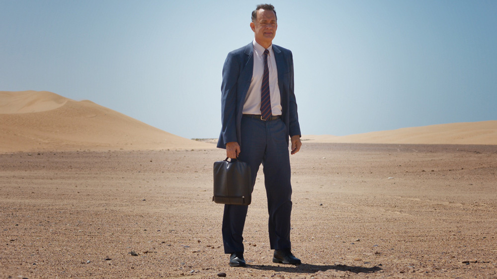 alan clay standing out in the desert in a suit and holding a briefcase
