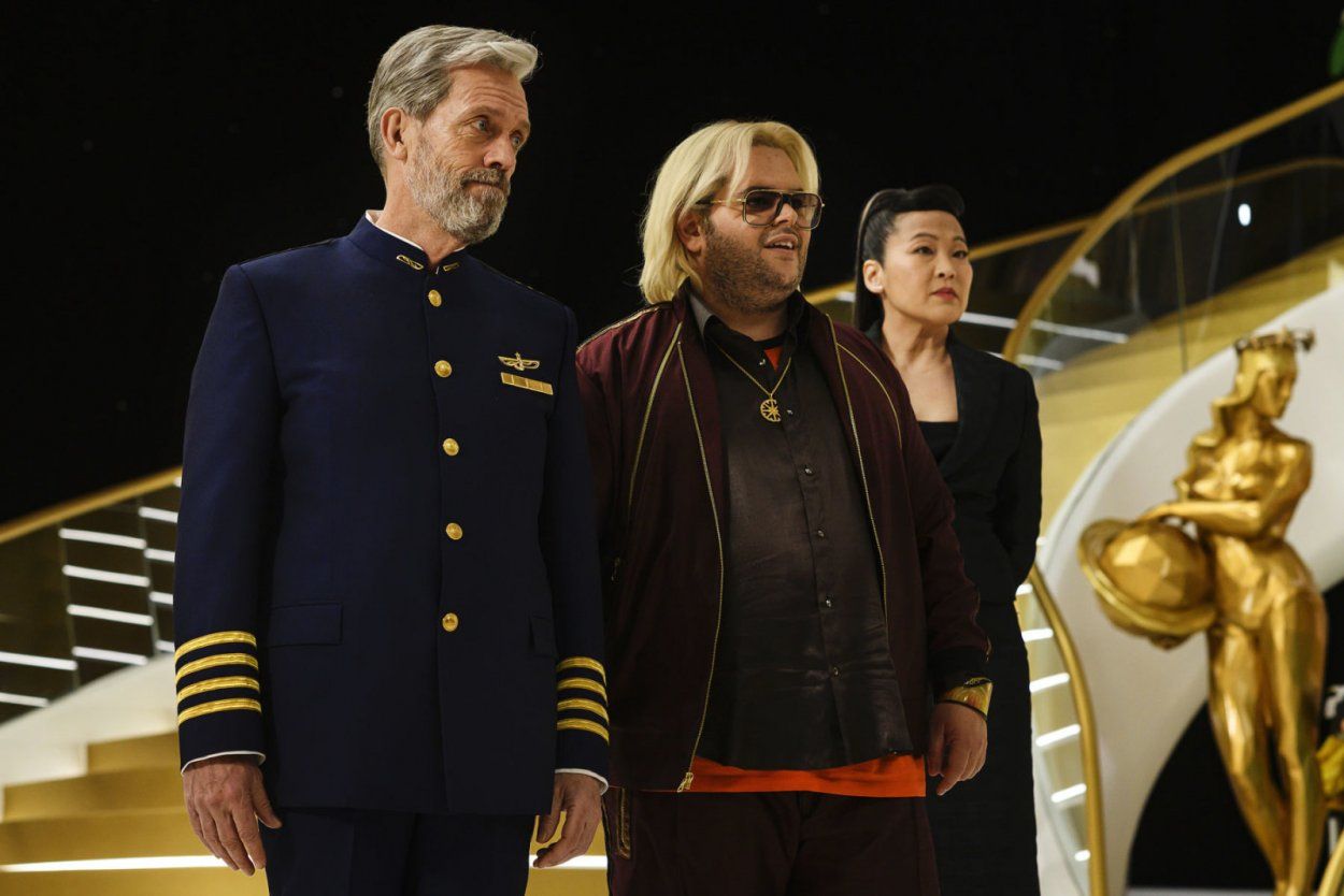 Ryan (Hugh Laurie), Judd (Josh Gad) and Iris (Suzy Nakamura) greet the passengers on the main deck of the ship.