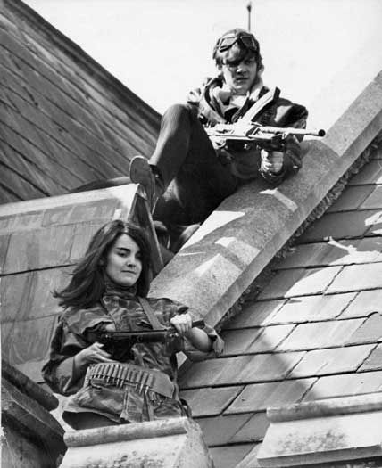 Mick and The Girl stand on the roof of the school, guns poised