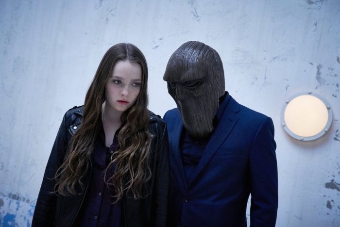 Margot stands looking in a corner while a man in a blue suit and creepy wooden mask circles closely to her.