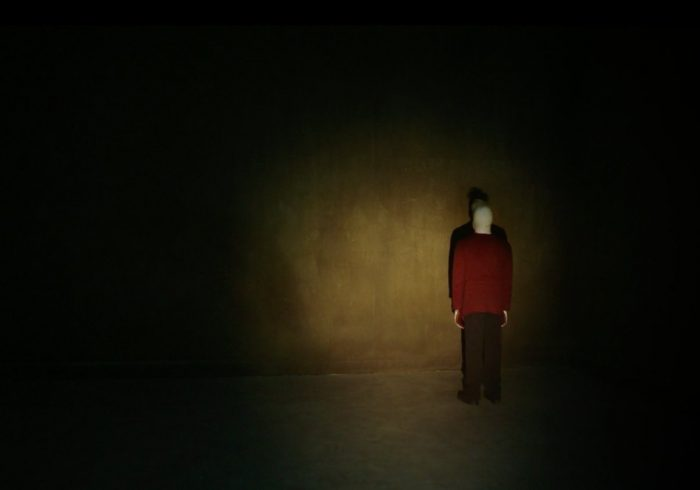 Pretzel Jack, an albino person with a red sweater and brown pants, stands in a corner of a dark room, illuminated only by a flashlight