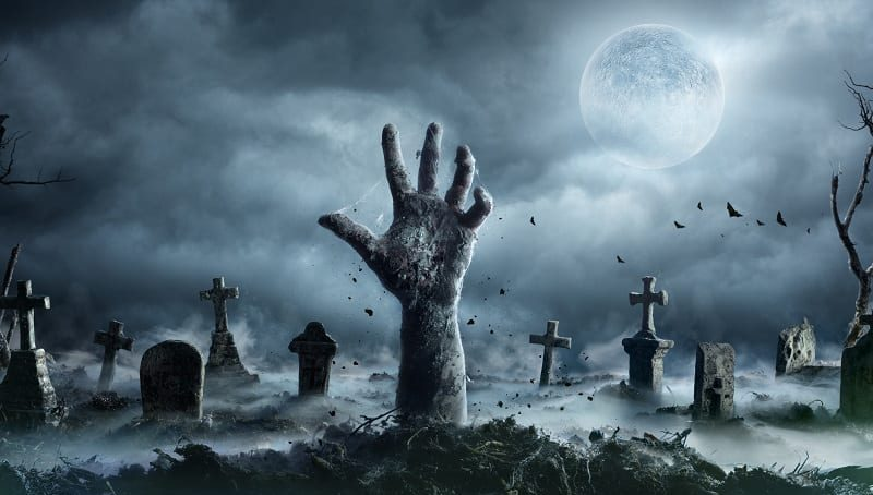 a hand reaches out from a grave at night with moon shining