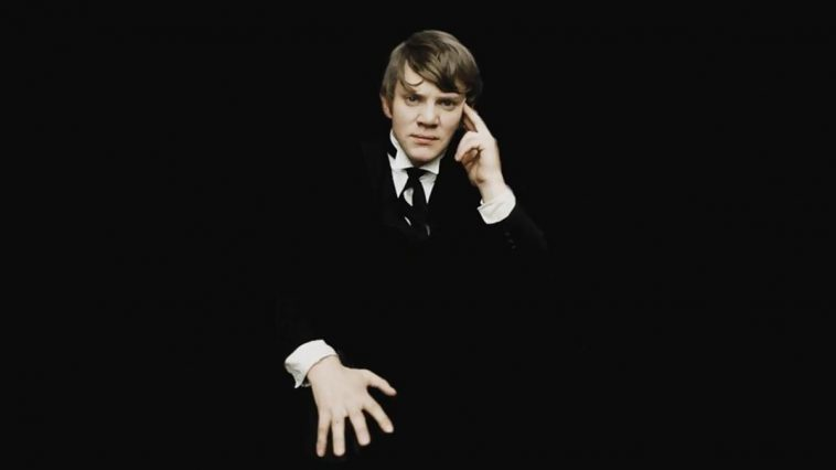 Malcolm McDowell in public school uniform poses cockily against a black background