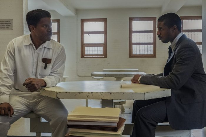 Walter McMillian looks skeptically at attorney Bryan Stevenson in a prison visitation room.