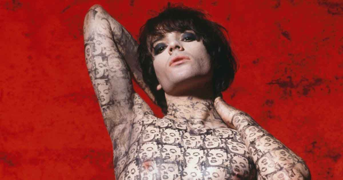 Richey Edwards poses against a red background, his body covered in Marilyn Monroe tattoos
