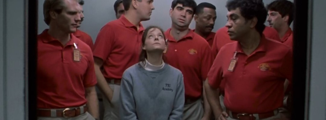 Starling stands in an elevator, surrounded by very tall male students