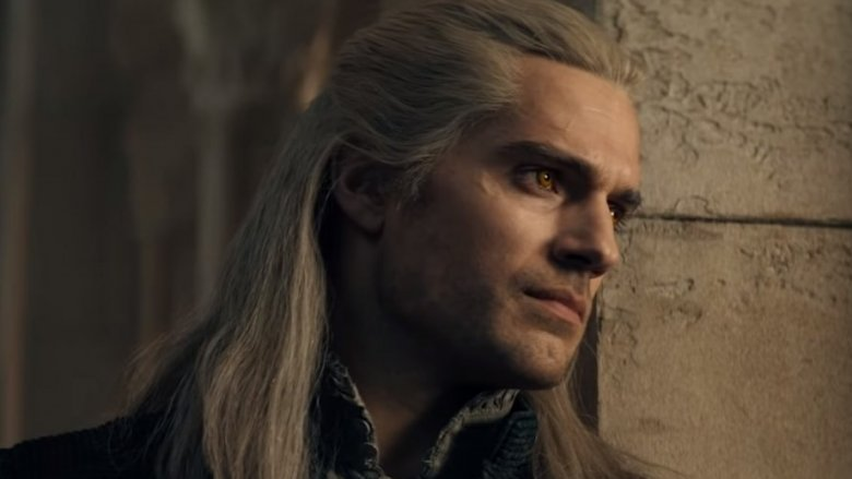 Geralt (Henry Cavill) leans against a wall, the camera close on his face.