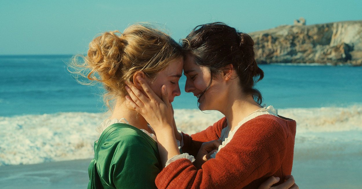 Marianne and Heloise holding each other in embrace on a beach