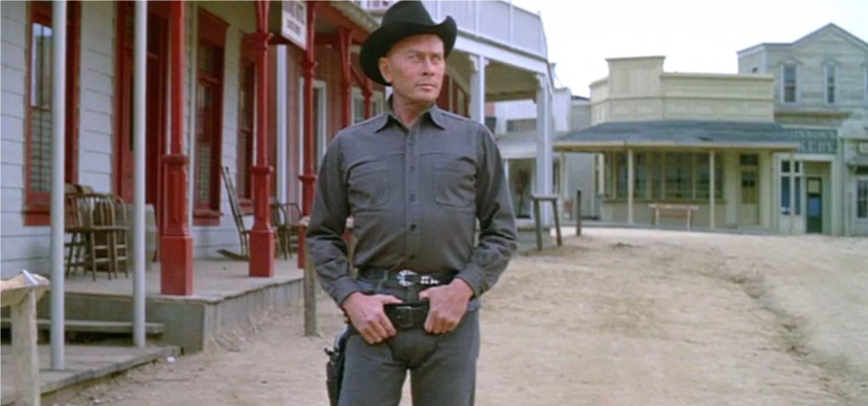 The Gunslinger stands in the road with his hands in his gun belt.
