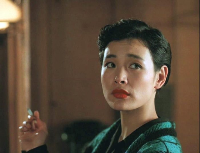 Josie Packard stares off camera holding a cigarette