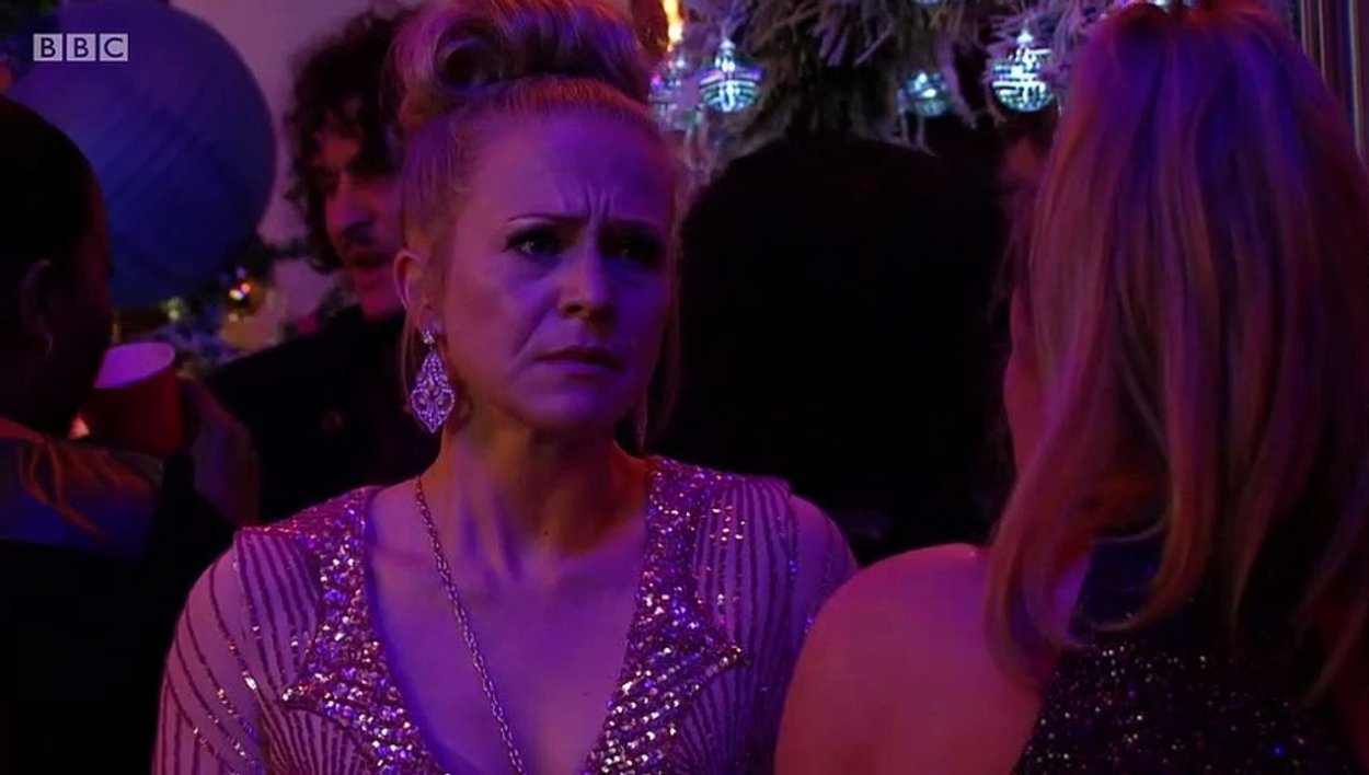 Linda looks desperately sad at a party wearing a pink sparkly dress