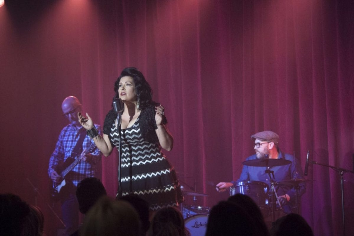 Del Rio wears a black and white chevron dress, hands outstretched. Her band mates are lit in purple, and red drapes flank them.