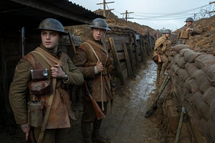 Four soldiers look at something off screen while standing in a trench