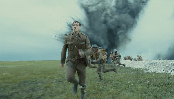 Scofield runs on a field with an explosion and fellow soldiers behind him