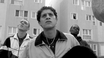 Vinz, Saïd and Hubert stand in front of a tower block