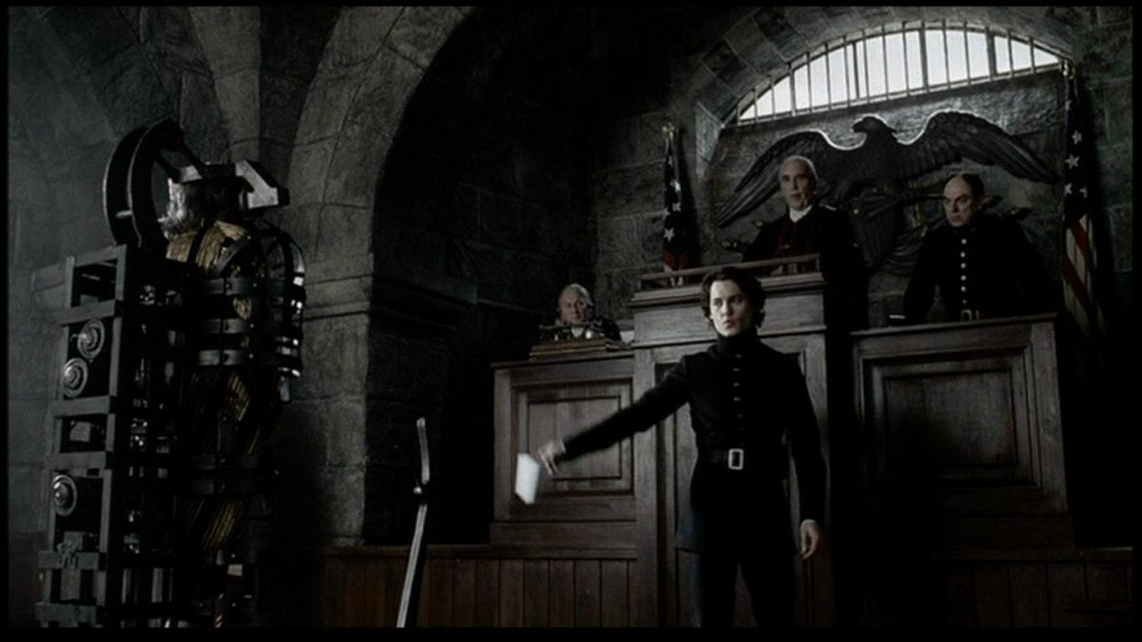 Ichabod Crane stands before a man in restraints in front of a judge in a gotic styled courtroom