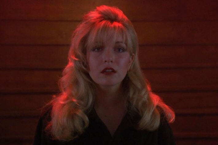 A closeup of Laura Palmer, against a background of a brick wall. Her expression is pained and heartbreaking.