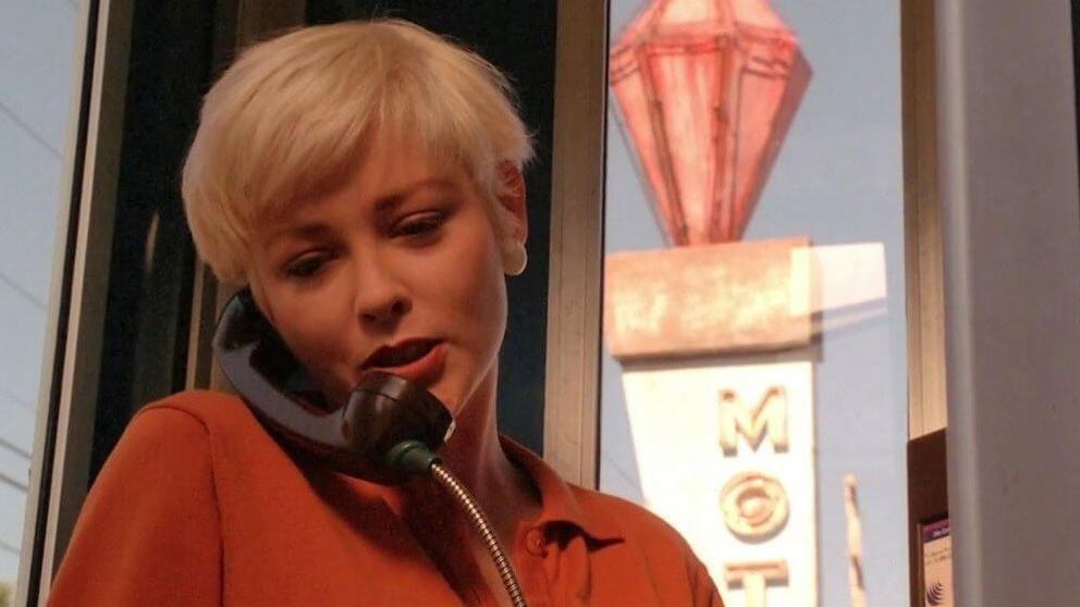 Teresa on a pay phone outside a motel