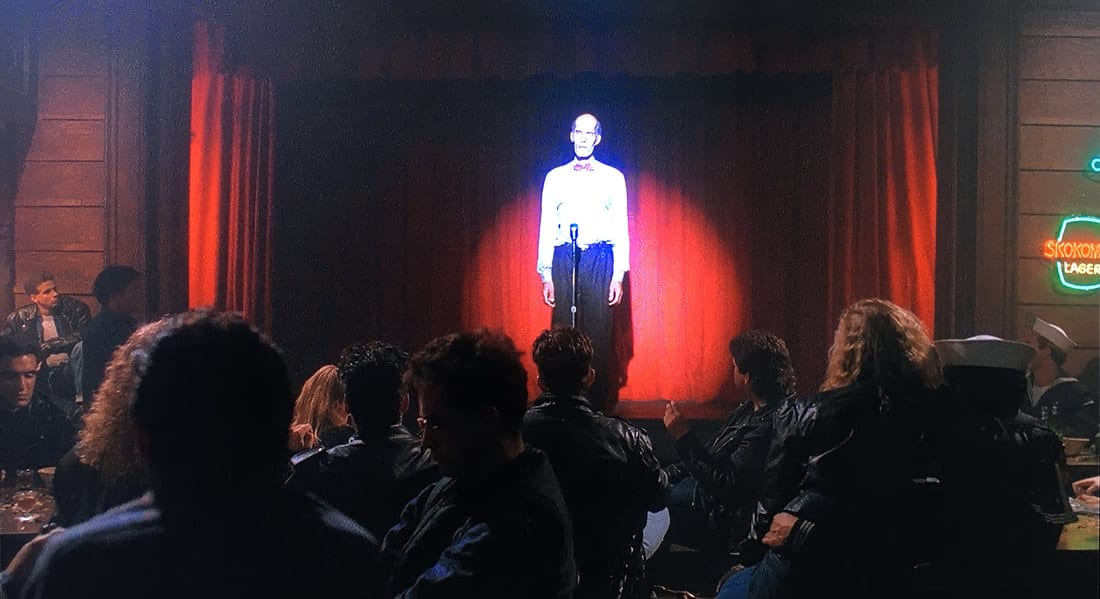 From the back of the Roadhouse you can see the tall giant on stage, in front of red curtains with a spotlight on him.