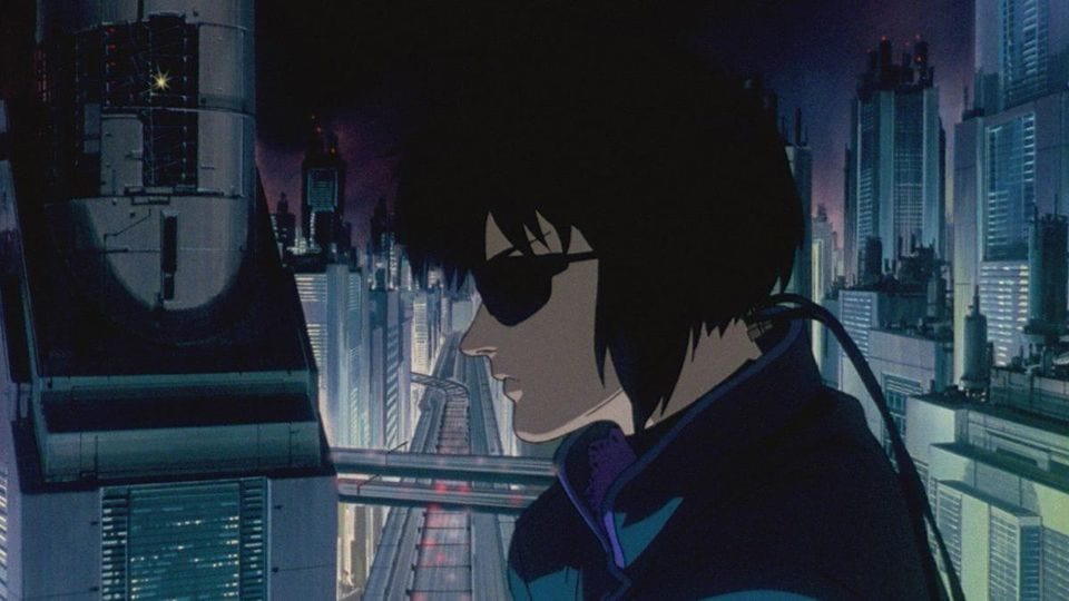 Kusanagi sits, plugged into the network with the city skyline behind her