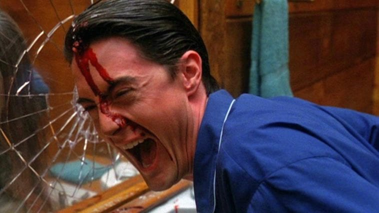Cooper laughs maniacally with blood on his face after breaking a mirror with his head