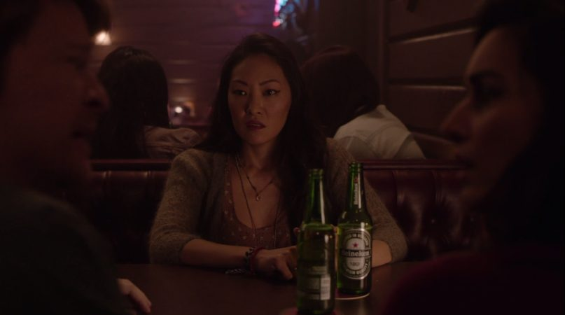 Abbie sits, looking to the side pensively, a few beer bottles in front of her already.