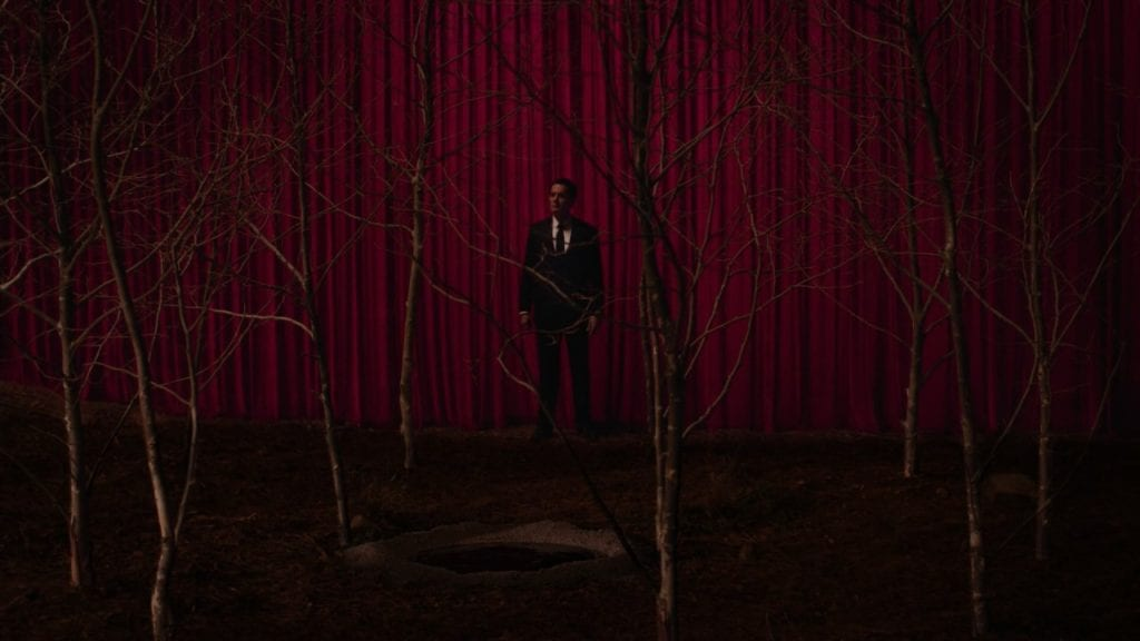 Cooper stands between a grove of sycamores and a red curtain.
